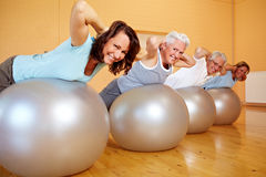 Group using Swiss balls. Group in gym doing back exercises on Swiss balls Royalty Free Stock Image