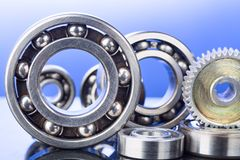 Group of various ball bearings and gears close up on nice blue background with reflections Royalty Free Stock Images