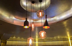 Group of Various Modern Style Black Metal and Glass Illuminated Lamps Hanging on The Ceiling Royalty Free Stock Photos