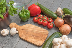 Group of vegetables lying on the table. Olive cutting board, peppers, tomatoes, onion, garlic, zucchini, cucumber, eggplant, basil and mushrooms are lying on the Stock Photography