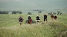Group of Viking with shields walking forward on the meadow