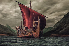 Group of vikings are floating on the sea on Drakkar with mountains on the background Royalty Free Stock Image