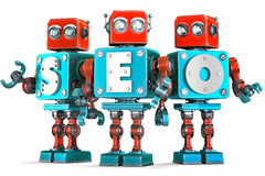 Group of vintage robots with SEO sign. SEO optimization concept. Isolated. Contains clipping path. Group of vintage robots with SEO sign. SEO optimization Royalty Free Stock Images