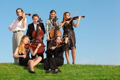 Group of  violinists play on  grass against sky. Group of  violinists play on green grass against sky Stock Image