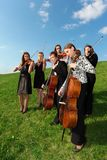 Group of violinists play standing on grass. Group of violinists play standing on green grass Stock Photo