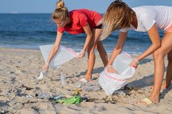 Group of volunteers cleaning up beach line. People tidying up rubbish on sea shore. Ecology concept. Group of volunteers cleaning up beach line. Volunteers stock photo