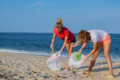 Group of volunteers cleaning up beach line. People tidying up rubbish on sea shore. Ecology concept. Group of volunteers cleaning up beach line. Volunteers royalty free stock photography