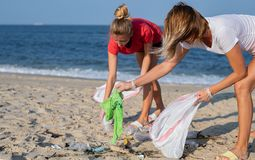 Group of volunteers cleaning up beach line. People tidying up rubbish on sea shore. Ecology concept. Group of volunteers cleaning up beach line. Volunteers royalty free stock images