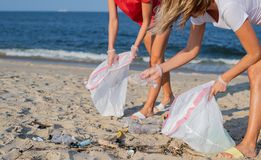 Group of volunteers cleaning up beach line. People tidying up rubbish on sea shore. Ecology concept. Group of volunteers cleaning up beach line. Volunteers royalty free stock photos