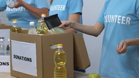 Group of volunteers packing food in donation boxes, working in social center stock video