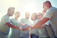 Group of volunteers putting hands on top outdoors Stock Photos