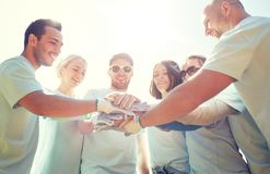 Group of volunteers putting hands on top outdoors royalty free stock images