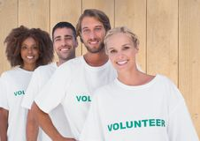 Group of volunteers standing against wooden background. Portrait of group of volunteers standing against wooden background Stock Photo