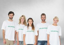 Group of volunteers standing in front of blank grey background royalty free stock photo