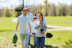 Group of volunteers with trees and rake in park Royalty Free Stock Image