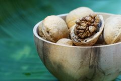 Group of walnut in wooden bowl on wood background, copy space, super food concept. Group of walnuts and a crack nut in wooden bowl on wood background, copy space royalty free stock photo