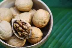 Group of walnut in wooden bowl on wood background, copy space, super food concept. Group of walnuts and a crack nut in wooden bowl on wood background, copy space stock photos