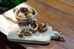 Group of walnut in wooden bowl on wood background, copy space, super food concept. Group of walnuts and a crack nut in wooden bowl on wood background, copy space stock photo
