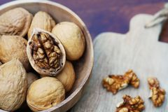 Group of walnut in wooden bowl on wood background, copy space, super food concept. Group of walnuts and a crack nut in wooden bowl on wood background, copy space stock image
