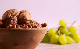 Group of walnuts and grapes. Close up photo of a part of a group of walnuts into a wood bowl, a group of unfocused green grapes at the back, all over wood board royalty free stock photography