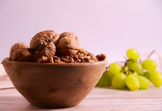 Group of walnuts and grapes. Close up photo of a group of walnuts into a wood bowl, a group of unfocused green grapes at the back, all over wood board, and white stock photo