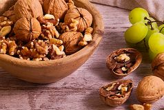 Group of walnuts and grapes. 45 degrees photo of group of walnuts into wood bowl and some walnuts and a group of green grapes beside, all over wood board and stock image