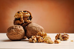 Group of walnuts on a table with brown background. Group of walnuts on a white wooden table with brown background Stock Photos