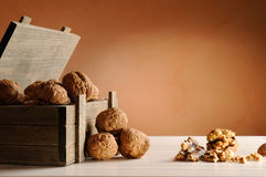 Group of walnuts on a table with trunk wooden container. Group of walnuts on a white table with trunk wooden container and brown background Royalty Free Stock Photo