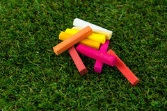 GROUP OF WARM TONE CHALK. A group of chalk in wam tone colored. put down on grass, close-up view Stock Image