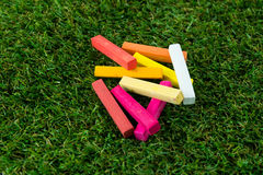 GROUP OF WARM TONE CHALK. A group of chalk in wam tone colored. put down on grass, close-up view Stock Photo
