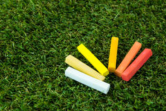 GROUP OF WARM TONE CHALK. A group of chalk in wam tone colored. put down on grass, close-up view Royalty Free Stock Images
