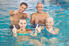 Group in water holding thumbs up. Happy group with senior couple in water holding their thumbs up royalty free stock images