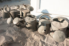 Group of watering cans. Group of rusted watering cans on the sand Royalty Free Stock Photos