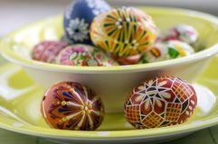 Group of wax painted Easter eggs in green spotted bowl stock photography