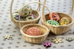 Group of wax painted Easter eggs in light brown wicker baskets, wax flower ornaments, traditional decoration. On brown spoted table, wooden flowers royalty free stock photography