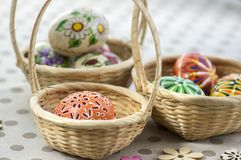 Group of wax painted Easter eggs in light brown wicker baskets, wax flower ornaments, traditional decoration. On brown spoted table, wooden flowers stock photography
