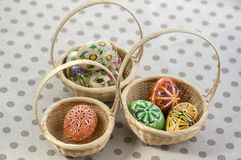 Group of wax painted Easter eggs in light brown wicker baskets, wax flower ornaments, traditional decoration. On brown spoted table royalty free stock photos