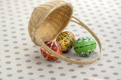 Group of wax painted Easter eggs spilled from light brown wicker baskets, wax flower ornaments, traditional decoration. On brown spoted table stock photo