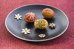Group of wax painted Easter eggs spread on black plate, flower ornaments, traditional decoration. On red tablecloth, wooden flowers stock photography