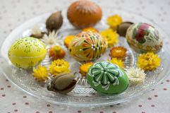 Group of wax painted Easter eggs spread on white transparent plate, flower ornaments, traditional decoration. On brown spoted tablecloth royalty free stock photos