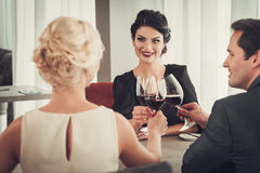 Group of wealthy people clinking glasses of red wine in restaurant Stock Photography