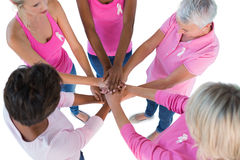 Group wearing pink and ribbons for breast cancer with hands toge Royalty Free Stock Images