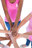 Group wearing pink and ribbons for breast cancer putting hands t Stock Photography