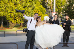 A group of wedding photographers on the streets of Budapest is holding a photo session for a couple of newlyweds. Stock Photos