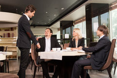 Group of well dressed business people greeting  handsome busines Stock Images