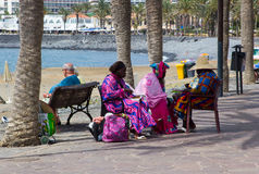A group of West African sisters enjoy a well earned snack as the take a rest from their hair plaiting business for tourists on the Stock Photography
