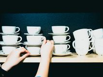 Group of white coffee cup arrange on wooden shelf in coffee shop Royalty Free Stock Photo