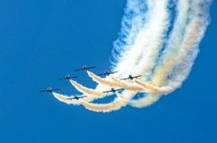 Group of white fighter jet airplane with a trace of white smoke against a blue sky. Stock Image