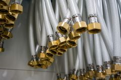 Group of white flexible rubber hose with brass nut connector stock photography