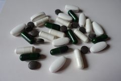 Group of white, green and black pills. Group of white, green and black tablets and capsules royalty free stock photos